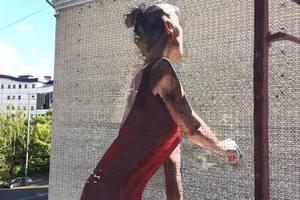 В Киеве появился новый мурал: девушка в красном платье стоит у открытого окна