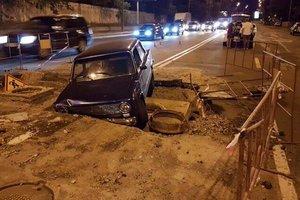 В Киеве автомобиль нырнул в огромную яму среди дороги