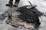 Затопленную трассу Киев-Чоп начали латать: асфальт кладут прямо в лужи