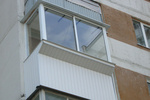В Киеве мужчина свесил ноги с балкона и зовет на помощь