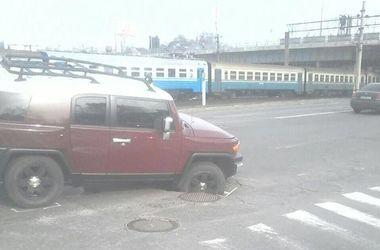 В Киеве дорогой внедорожник провалился в яму на дороге
