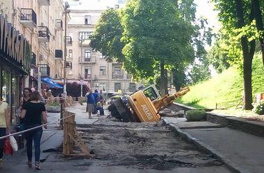 В центре Киева трактор провалился в яму в асфальте