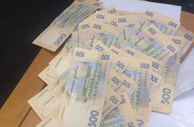 В Киеве двух чиновников поймали после получения 100 тыс. грн взятки
