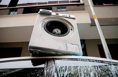 Мужчина в гневе сбросил стиральную машину на автомобиль