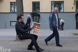 Необычный фокус: розыгрыш с невидимым стулом посреди улицы озадачил прохожих