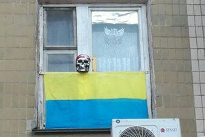 From Kiev adorned the window of the apartment upside-down flag and skull