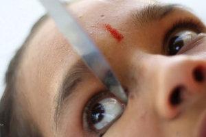 Девушка-йог наносит макияж на глаза зажатым коленями ножом