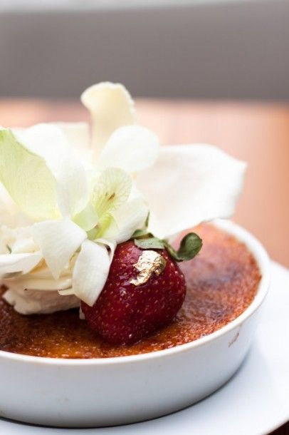 creme-brulee-decorate-with-white-petals-on-white-plate_1428-153