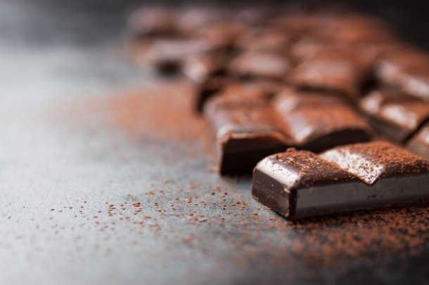 pieces-of-chocolate-tablet-on-a-black-wooden-table-and-cacao-sprinkled-on-top_1220-538_01