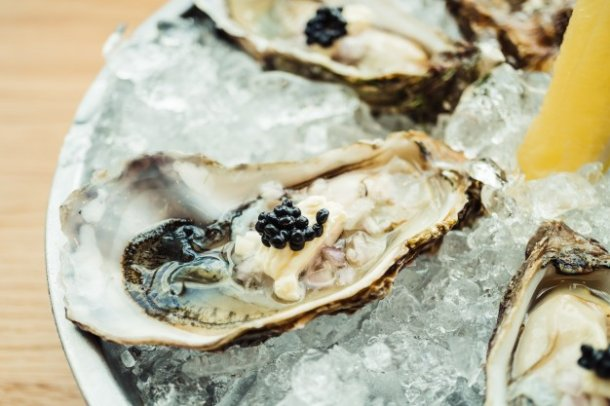raw-and-fresh-oyster-with-caviar-on-top-and-lemon_1203-10310