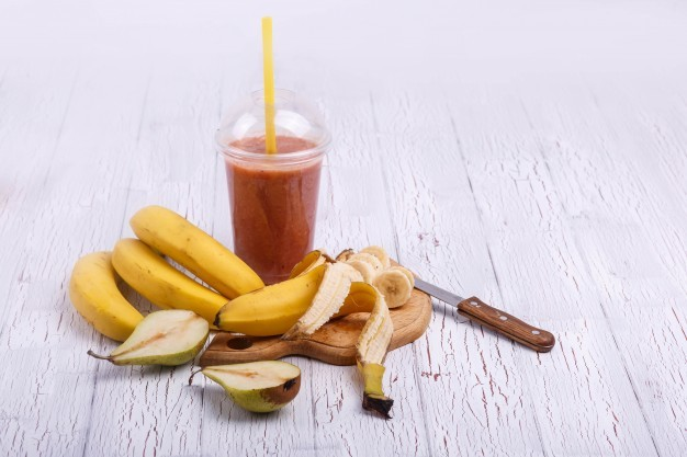 red-detox-coctail-with-bananas-on-chopping-board-lies-on-white-table_1304-3502