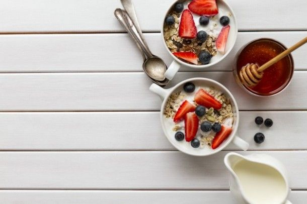 tasty-colorful-breakfast-with-oatmeal-yogurt-strawberry-blueberry-honey-and-milk-on-white-wooden-background-with-copy-space-top-view_1220-1506