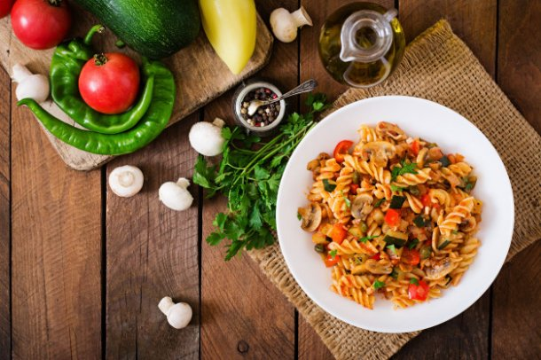 vegetarian-vegetable-pasta-fusilli-with-zucchini-mushrooms-and-capers-in-white-bowl-on-wooden-table_2829-432