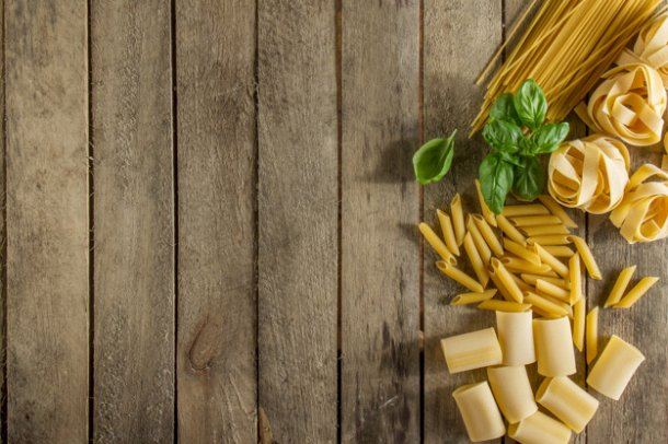 wooden-background-with-italian-pasta-and-basil_23-2147606554