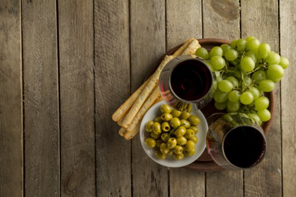wooden-surface-with-olives-grapes-and-wine-glasses_23-2147612091
