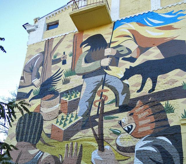 Необычный флаг можно увидеть на мурале около Пейзажной аллеи. Мурал находится в Десятинном переулке и выполнен в стиле мексиканской мифологии. Там изображен человек с головой орла, который держит в руках украинский флаг. Создатель, аргентинский художник Франко Фасоли, заверяет, что хотел таким образом поддержать нашу страну и показать, как он восхищается ее силой и стойкостью. Фото: vkieve.net