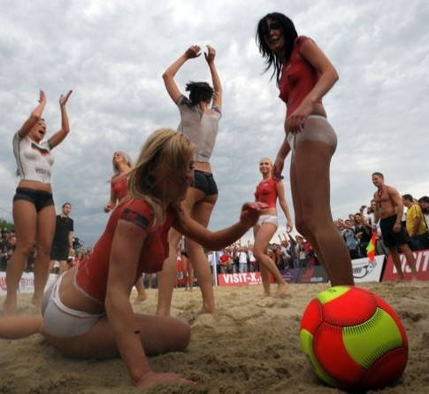 Topless porn actresses wearing bodypaint with German colours play a  beach football game on a beach in Vienna, on June 15, 2008, a day before the European football championship, group B football match between Austria and Germany.  AFP PHOTO / JOE KLAMAR