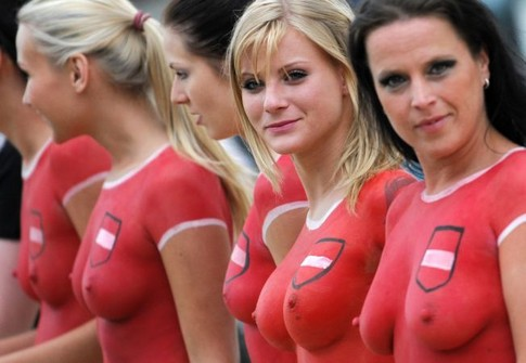 Topless porn actresses wearing body paint with the Austrian colours line up prior their match during beach football event in Vienna on June 15, 2008 a day before the European football championship, group B football match between Austria and Germany.   AFP PHOTO / JOE KLAMAR