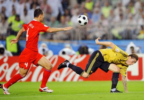 Russian defender Sergei Ignashevich (L) eyes the ball as Spanish forward Fernando Torres tumbles forward during the Euro 2008 championships semi-final football match Russia vs. Spain on June 26, 2008 at Ernst-Happel stadium in Vienna, Austria. AFP PHOTO / FRANCK FIFE -- MOBILE SERVICES OUT --
