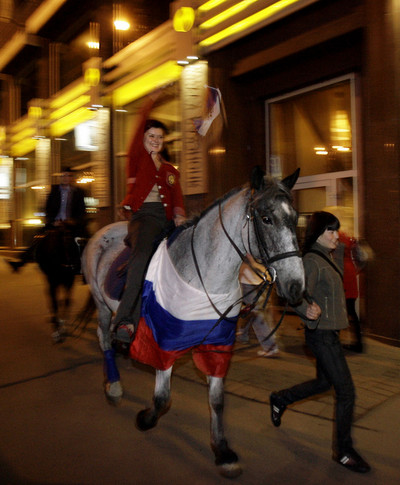 A Russian football fan ride a horse draped in a Russian flag celebrates after the Euro 2008 semi-final match between Russia and Spain in Moscow early June 27, 2008. Despite Spain's 3-0 win, it has been more than 20 years since Russia has had such a serious presence on the international footabll stage and many citizens are proud of their team's performance.      AFP PHOTO / DIMA KOROTAYEV (Photo credit should read DIMA KOROTAYEV/AFP/Getty Images)