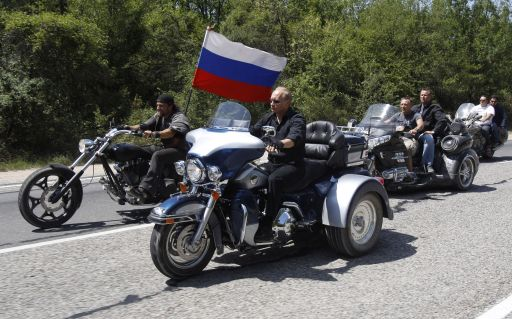 Russia's Prime Minister Vladimir Putin (2L) rides Harley Davidson Lehman Trike as he arrives for the meeting with Russian and Ukrainian motorbikers at their camp near Sevastopol in Ukraine's Crimea on July 24, 2010.  AFP PHOTO / POOL / SERGEI KARPUKHIN