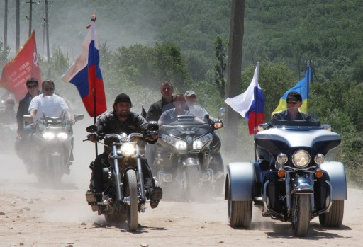 Russia's Prime Minister Vladimir Putin (R) rides a Harley Davidson Lehman Trike as he visits Russian and Ukrainian motorbikers at their camp near Sevastopol in Ukraine's Crimea on July 24, 2010. AFP PHOTO / Vasiliy BATANOV