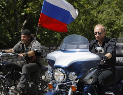 Russia's Prime Minister Vladimir Putin (R) rides a Harley Davidson Lehman Trike as he arrives for the meeting with Russian and Ukrainian motorbikers at their camp near Sevastopol in Ukraine's Crimea on July 24, 2010.  AFP PHOTO / POOL / SERGEI KARPUKHIN