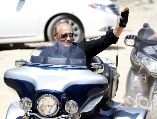 Russia's Prime Minister Vladimir Putin waves while riding Harley Davidson Lehman Trike as he arrives for the meeting with Russian and Ukrainian motorbikers at their camp near Sevastopol in Ukraine's Crimea on July 24, 2010.  AFP PHOTO / POOL / SERGEI KARPUKHIN