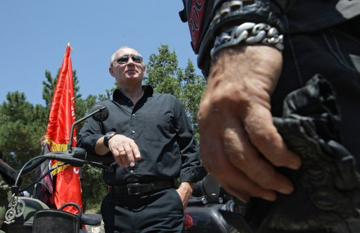 Russia's Prime Minister Vladimir Putin (L) visits the meeting with Russian and Ukrainian motorbikers at their camp near Sevastopol in Ukraine's Crimea on July 24, 2010.  AFP PHOTO / RIA NOVOSTI / POOL / ALEXEY DRUZHININ