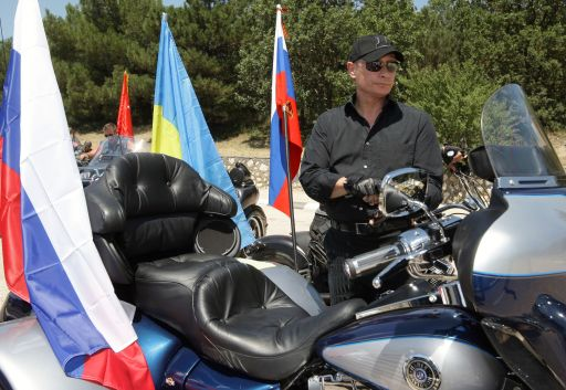 "Russia's Prime Minister Vladimir Putin arrives at a rally with Russian and Ukrainian motorbikers at their camp near Sevastopol in Ukraine's Crimea on July 24, 2010.  Leaving a cloud of dust in his wake, a black-clad Russian Prime Minister Vladimir Putin roared into a rally in Ukraine on a Harley Davidson and hailed bikes as a ""symbol of freedom"". AFP PHOTO / RIA NOVOSTI / POOL / ALEXEY DRUZHININ"