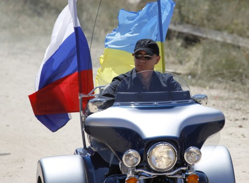 "Russia's Prime Minister Vladimir Putin rides Harley Davidson Lehman Trike decorated with Russian and Ukrainian national flags as he arrives for the meeting with motorbikers at their camp near Sevastopol in Ukraine's Crimea on July 24, 2010. Leaving a cloud of dust in his wake, a black-clad Russian Prime Minister Vladimir Putin roared into a rally in Ukraine on a Harley Davidson and hailed bikes as a ""symbol of freedom"". AFP PHOTO / POOL / SERGEI KARPUKHIN"