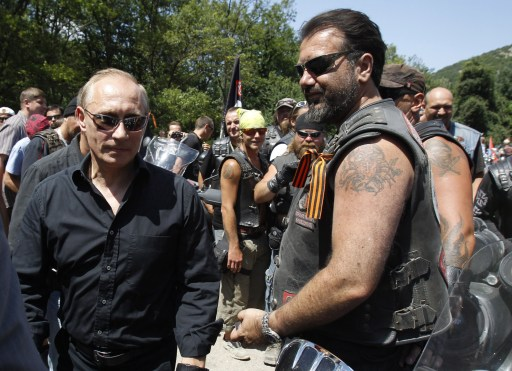 "Russia's Prime Minister Vladimir Putin (L) meets with Russian and Ukrainian motorbikers at their camp near Sevastopol in Ukraine's Crimea on July 24, 2010. Leaving a cloud of dust in his wake, a black-clad Russian Prime Minister Vladimir Putin roared into a rally in Ukraine on a Harley Davidson and hailed bikes as a ""symbol of freedom"". AFP PHOTO / POOL / SERGEI KARPUKHIN"