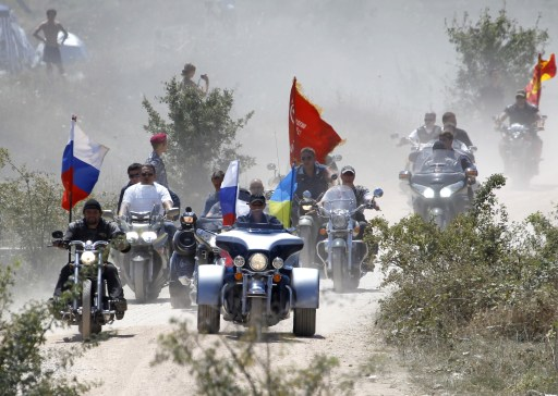 Russia's Prime Minister Vladimir Putin (C) rides a Harley Davidson Lehman Trike decorated with the Russian and Ukrainian national flags as he arrives for the meeting with motorbikers at their camp near Sevastopol in Ukraine's Crimea on July 24, 2010.  AFP PHOTO / POOL / SERGEI KARPUKHIN