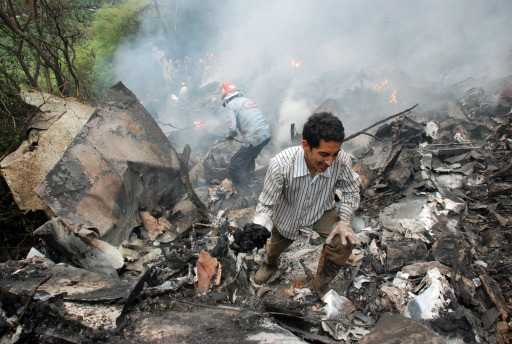 Pakistani rescue workers search for survivors in wreckage of a crashed passenger plane at The Margalla Hills on the outskirts of Islamabad on July 28, 2010.    A Pakistani airliner carrying 152 people crashed in a ball of flames into densely wooded hills outside Islamabad amid heavy rain and poor visibility, killing everyone on board. Rescue officials said pieces of charred flesh and body parts were littered around the smouldering wreckage, partially buried on a remote hillside, in the deadliest crash involving a Pakistani passenger jet in 18 years.   AFP PHOTO/ADIL KHAN