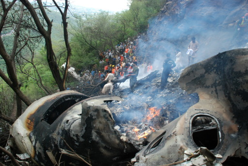 Pakistani rescue workers search for survivors in the wreckage of a crashed passenger plane at The Margalla Hills on the outskirts of Islamabad on July 28, 2010.    A Pakistani airliner carrying 152 people crashed in a ball of flames into densely wooded hills outside Islamabad amid heavy rain and poor visibility, killing everyone on board. Rescue officials said pieces of charred flesh and body parts were littered around the smouldering wreckage, partially buried on a remote hillside, in the deadliest crash involving a Pakistani passenger jet in 18 years.   AFP PHOTO/ADIL KHAN