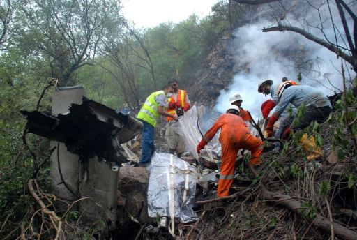 Pakistani rescue workers search for survivors in the wreckage of a crashed passenger plane in the Margalla Hills on the outskirts of Islamabad on July 28, 2010. A Pakistani airliner carrying 152 people crashed in a ball of flames into densely wooded hills outside Islamabad amid heavy rain and poor visibility, killing everyone on board. Rescue officials said pieces of charred flesh and body parts were littered around the smouldering wreckage, partially buried on a remote hillside, in the deadliest crash involving a Pakistani passenger jet in 18 years. AFP PHOTO/ADIL KHAN