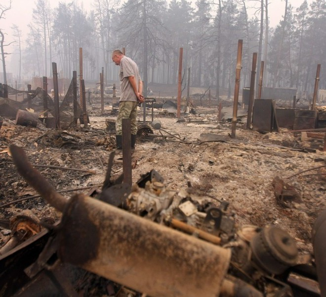 A man inspects ruins of his house in the village of Beloomut, some 130 kilometers from Moscow on July 31, 2010. Hundreds of thousands of firefighters, including army troops, battled forest fires raging across central Russia in the worst heatwave for decades, destroying houses and killing more than 30 people. A total of 238,000 firefighters are battling the flames in 14 regions, along with 226 aircraft, the emergency ministry said Saturday, calling the situation under control.  AFP PHOTO/ ANDREY SMIRNOV