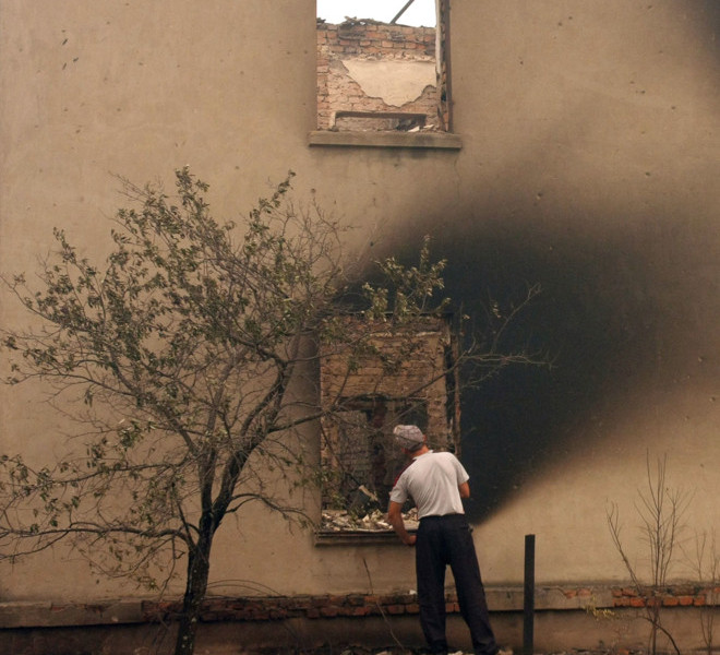 A man inspects a burnt building in the village of Beloomut, some 130 kilometers from Moscow on July 31, 2010. Hundreds of thousands of firefighters, including army troops, battled forest fires raging across central Russia in the worst heatwave for decades, destroying houses and killing more than 30 people. A total of 238,000 firefighters are battling the flames in 14 regions, along with 226 aircraft, the emergency ministry said Saturday, calling the situation under control.  AFP PHOTO/ ANDREY SMIRNOV