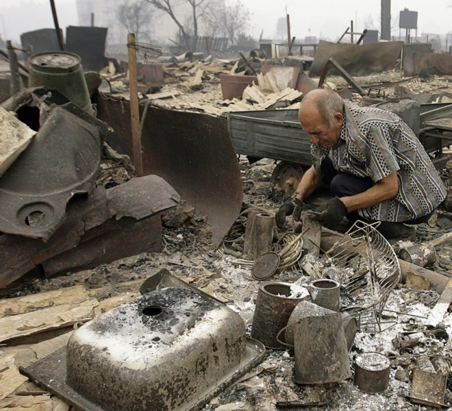 A man searches through the rubble for his belongings after a fire swept through the village of Mokhovoye, some 130 kilometers from Moscow on July 31, 2010. Hundreds of thousands of firefighters, including army troops, battled forest fires raging across central Russia in the worst heatwave for decades, destroying houses and killing more than 30 people. A total of 238,000 firefighters are battling the flames in 14 regions, along with 226 aircraft, the emergency ministry said Saturday, calling the situation under control. AFP PHOTO/ ARTYOM KOROTAYEV