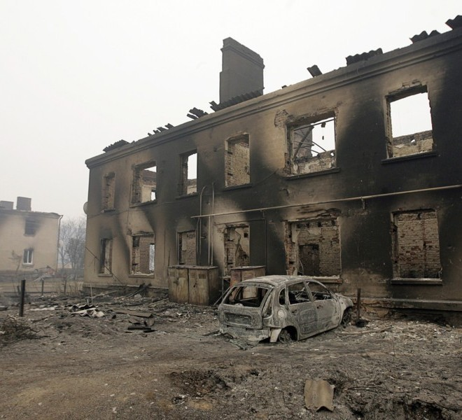 A burnt-out car sits in front of a destroyed house in the village of Mokhovoye, some 130 kilometers from Moscow on July 31, 2010. Hundreds of thousands of firefighters, including army troops, battle forest fires raging across central Russia in the worst heatwave for decades, destroying houses and killing more than 30 people. A total of 238,000 firefighters are battling the flames in 14 regions, along with 226 aircraft, the emergency ministry said Saturday, calling the situation under control. AFP PHOTO/ ARTYOM KOROTAYEV