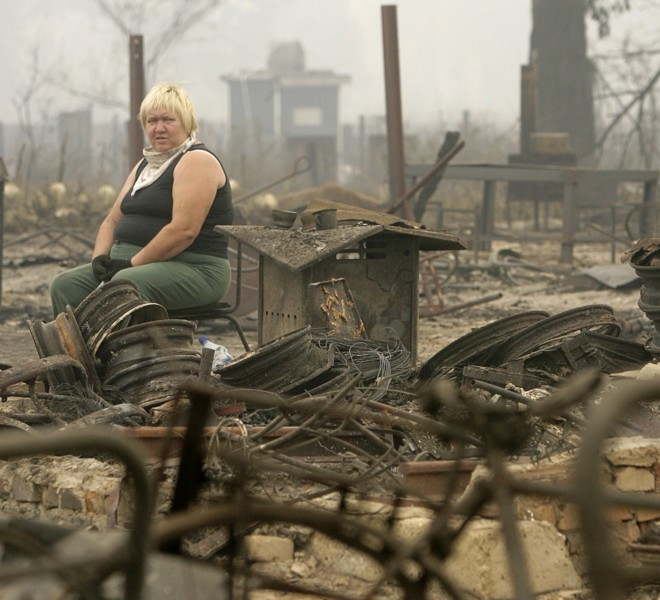 A woman sits surrounded by the remains of her house in the village of Mokhovoye, some 130 kilometers from Moscow on July 31, 2010. Hundreds of thousands of firefighters, including army troops, battled forest fires raging across central Russia in the worst heatwave for decades, destroying houses and killing more than 30 people. A total of 238,000 firefighters are battling the flames in 14 regions, along with 226 aircraft, the emergency ministry said Saturday, calling the situation under control. AFP PHOTO/ ARTYOM KOROTAYEV