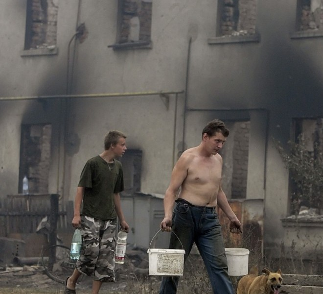People pass by a destriyed house in the village of Mokhovoye, some 130 kilometers from Moscow on July 31, 2010. Hundreds of thousands of firefighters, including army troops, battled forest fires raging across central Russia in the worst heatwave for decades, destroying houses and killing more than 30 people. A total of 238,000 firefighters are battling the flames in 14 regions, along with 226 aircraft, the emergency ministry said Saturday, calling the situation under control. AFP PHOTO/ ARTYOM KOROTAYEV
