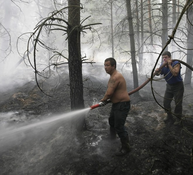 A firefighter doses flames amidst trees in the village of Lesnoye, some 130 kilometers from Moscow on July 31, 2010. Hundreds of thousands of firefighters, including army troops, battled forest fires raging across central Russia in the worst heatwave for decades, destroying houses and killing more than 30 people. A total of 238,000 firefighters are battling the flames in 14 regions, along with 226 aircraft, the emergency ministry said Saturday, calling the situation under control. AFP PHOTO/ ARTYOM KOROTAYEV