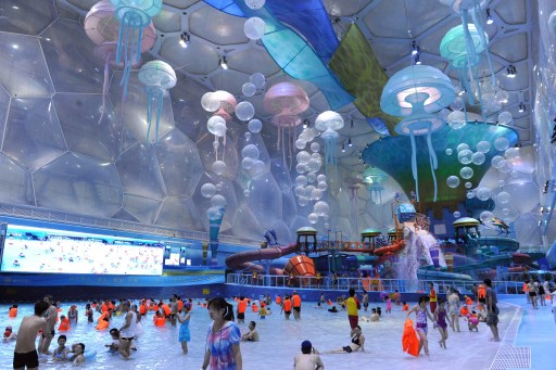 Visitors enjoy swimming in the newly re-launch National Aquatics Center, better known as the Water Cube, in Beijing on August 8, 2010. Adults have to pay 200 yuan (30 USD) to enter the park and a ticket for children will cost 160 yuan, a report said -- a high price in a city where the minimum wage comes to 960 yuan (145 USD) a month, as the Beijing's Olympic aquatic centre reopened as Asia's largest indoor water park. CHINA OUT   AFP PHOTO