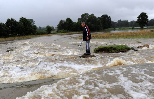 A man stands in flood waters in the south-western Polish town of Bogatynia inundated after the Miedzianka River burst it's banks, a result of heavy rains on August 7, 2010.  AFP PHOTO/ PAP/GRZEGORZ HAWALEJ