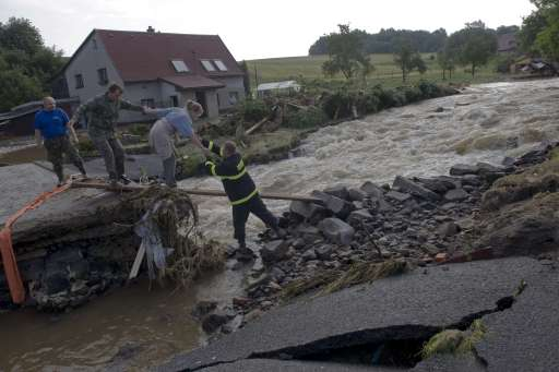 A firefighter helps residents of the Hermanice village to cross a flooded brook on August 8, 2010, near Liberec city, North Bohemia. Eight people died and thousands were evacuated amid disrupted traffic and power outages as floods hit parts of central Europe following heavy rainfall on August 7, 2010, rescuers said. AFP PHOTO MICHAL CIZEK