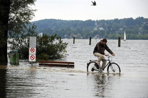 A man cycles over a flooded meadow  at the lakeshore of the Starnberger See lake in Starnberg, southern Germany, on August 7, 2010. Heavy rainfalls in southern parts of Bavaria caused floods.      AFP PHOTO    ANDREAS GEBERT    GERMANY OUT