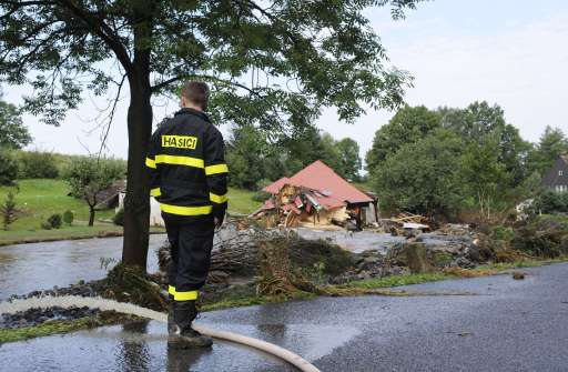 A firefighter looks at the flooded brook on August 8, 2010  in Hermanice village, near Liberec city, North Bohemia. Eight people died and thousands were evacuated amid disrupted traffic and power outages as floods hit parts of central Europe following heavy rainfall on August 7, 2010, rescuers said. AFP PHOTO/ MICHAL CIZEK