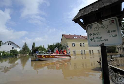 A boat of the German Lifeguard Association DLRG makes its way through the flood waters of the Neisse river in Ostritz near Goerlitz, eastern Germany, next to the Polish border on August 8, 2010. According to the authorities, 1,450 residents of Goerlitz and the surrounding area had been taken to safety in boats, buses and helicopters. Heavy rains and a dam-break on Witka Lake in Poland near the German border led the Neisse and several other rivers in Germany, Poland and the Czech Republic to burst their banks.     AFP PHOTO / ROBERT MICHAEL