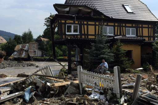 A resident of Bogadynia sits in front of his demaged house on August 8, 2010 in Bogadynia, southern Poland. Eight people died and thousands were evacuated amid disrupted traffic and power outages as floods hit parts of central Europe following heavy rainfall on August 7, 2010, rescuers said. AFP PHOTO/ MICHAL CIZEK